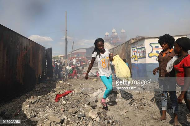 A woman carries a bag through rubble as Haitians desperately try to get into a burning shipping container to salvage clothes during a fire at...
