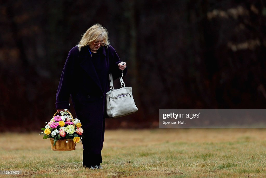 A woman carries a basket of flowers at the funeral services for six year-old Noah Pozner, who was killed in the shooting massacre in Newtown, CT, at B'nai Israel Cemetery on December 17, 2012 in Monroe, Connecticut. Today is the first day of funerals for some of the twenty children and seven adults who were killed by 20-year-old Adam Lanza on December 14, 2012.