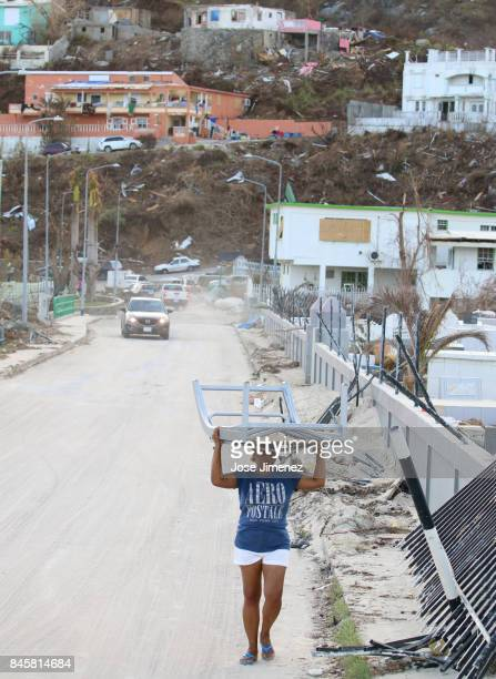 A woman carries a beach chair on September 11 2017 in Philipsburg St Maarten The Caribbean island sustained extensive damage from Hurricane Irma