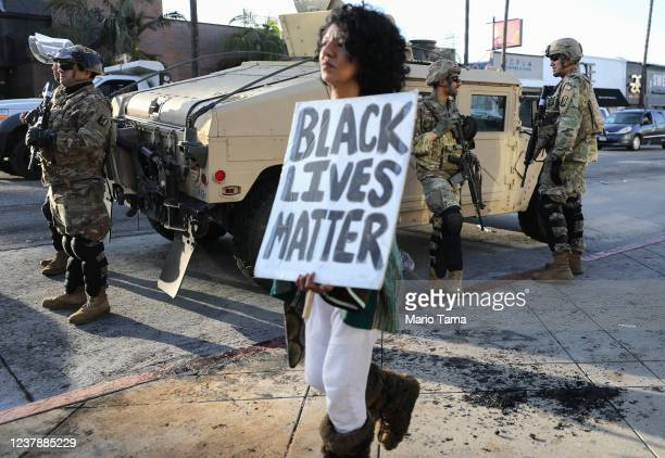 A woman carries a 'Black Lives Matter' sign past US National Guard troops in the Fairfax District an area damaged during yesterday's unrest after the...