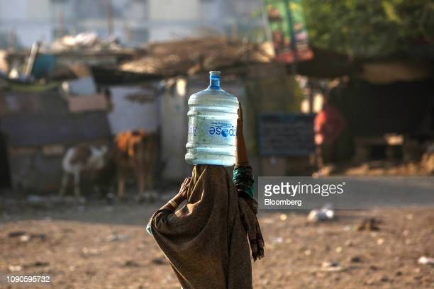 A woman carries a bottle filled with water on her head in Karachi Pakistan on Saturday Dec 22 2018 Women and children walk miles each day in search...