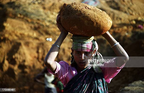 A woman carries a boulder on her head on the bank of Mari river in Jaflong Bangladesh The river coming from the Himalayas of India brings million...