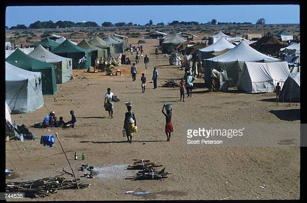 A woman carries a bowl on her head in a refugee camp March 24 1993 in Huambo Angola Despite a 1991 peace treaty the West African nation is again...