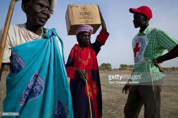 A woman carries a box home during an International Committee of the Red Cross distribution of seeds agricultural tools and food staples to households...
