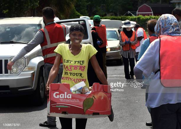 A woman carries a box of food she received from the Second Harvest Food Bank of Central Florida during a drivethru distribution event at the Islamic...