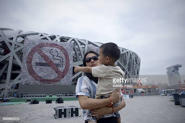 Woman carries a boy as she walks past a giant poster for World No Tobacco Day at the National Olympic Stadium or 'Birds Nest' in Beijing on May 31,...