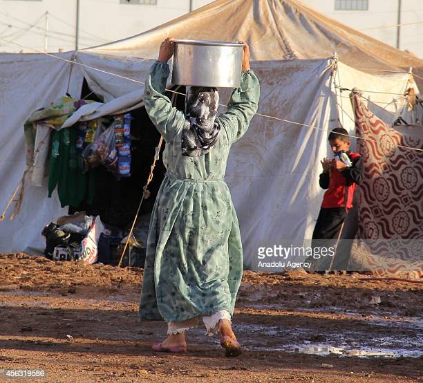 Woman carries a bucket at the top of her head at the tent city close to Al Salama border gate in Azez district of Aleppo, Syria on September 29, 2014.