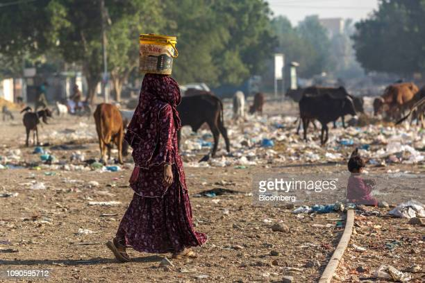 A woman carries a bucket filled with water on her head in Karachi Pakistan on Saturday Dec 22 2018 Women and children walk miles each day in search...