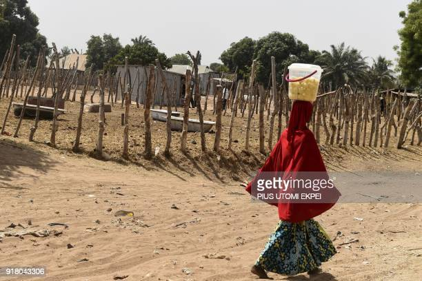 A woman carries a bucket of lemon on her head as she walka past an empty paddock at Benue cattle market in Makurdi capital of Benue State...
