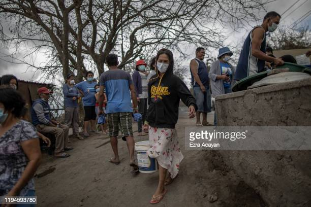 A woman carries a bucket of water as other residents wait along a highway to receive water and relief goods on January 19 2020 in the outskirts of...
