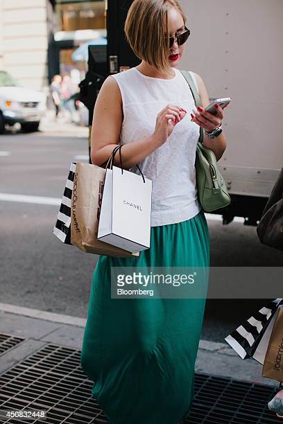 A woman carries a Chanel SA shopping bag while checking her mobile phone in the SoHo neighborhood of New York US on Wednesday June 18 2014 The...