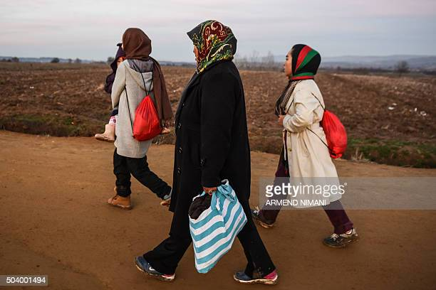 A woman carries a child as migrants and refugees walk on a road after crossing the Macedonian border into Serbia near the village of Miratovac on...