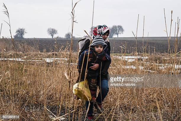 TOPSHOT A woman carries a child as she walks with other migrants after crossing the Macedonian border into Serbia near the village of Miratovac on...