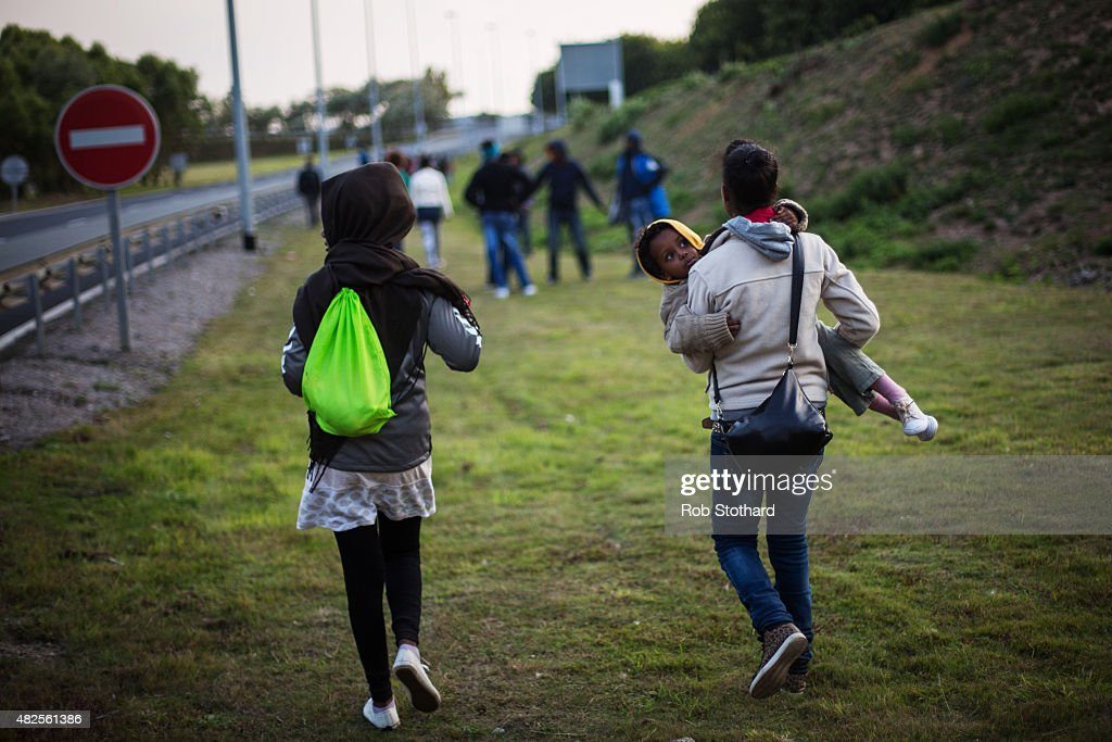 A woman carries a child as they walk towards the Eurotunnel terminal in Coquelles on July 31, 2015 in Calais, France. Hundreds of migrants are continuing to attempt to enter the Channel Tunnel and onto trains heading to the United Kingdom. Strike action and daily attempts by hundreds of migrants to enter the Channel Tunnel and onto trains heading to the United Kingdom is causing delays to passenger and freight services across the channel. British Prime Minster David Cameron has announced that extra sniffer dogs and fencing are to be sent to Calais and land owned by the Ministry of Defence is to be used as a lorry park to ease congestion near the port of Dover in Kent.