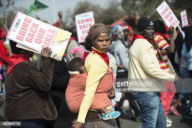 A woman carries a child on her back as hundreds of Soweto residents march and hold placards at the YMCA in Soweto Johannesbourg on May 22 to...