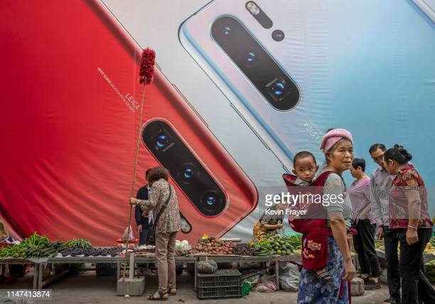 A woman carries a child pasased a billboard advertising smartphones for China's Huawei Technologies Co at a market on June 1 2019 in Mangshi Yunnan...