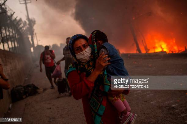 Woman carries a child past flames after a major fire broke out in the Moria migrants camp on the Greek Aegean island of Lesbos, on September 9, 2020....