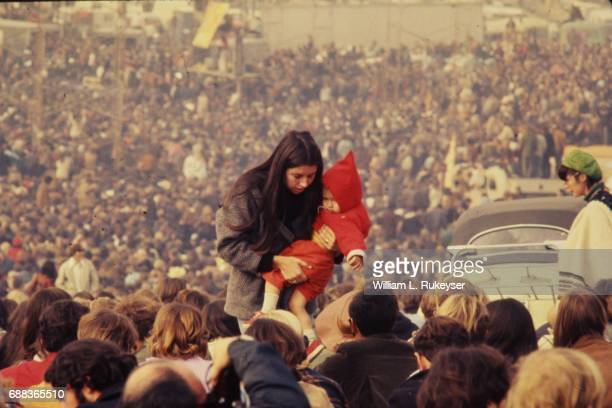 A woman carries a child through the massive audience at the Altamont Speedway prior to the free concert headlined by the Rolling Stones