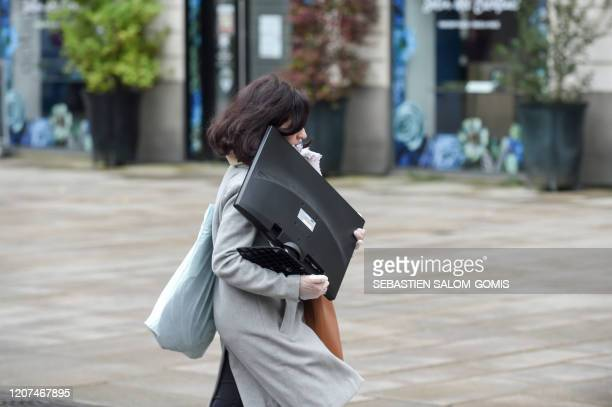 A woman carries a computer monitor for teleworking in Nantes western France on March 17 2020 while a strict lockdown comes into effect to stop the...