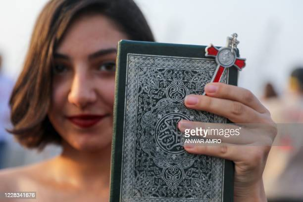 Woman carries a crucifix and a copy of the Koran during during a demonstration marking one month since the cataclysmic August 4 explosion that killed...