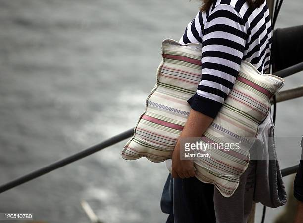 A woman carries a cushion as she arrives to see Cyrano De Bergerac presented by Shattered Windscreen Theatre Company at the Minack Theatre on August...
