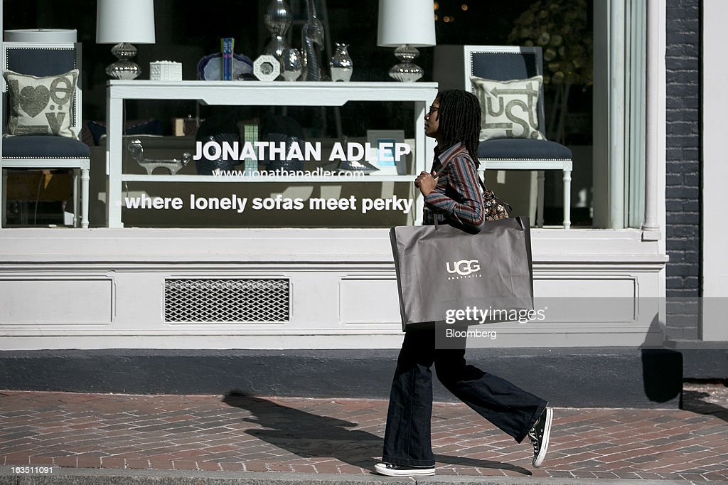 A woman carries a Deckers Outdoor Corp. Ugg brand shopping bag past a Jonathan Adler Enterprises LLC store in the Georgetown neighborhood of Washington, D.C., U.S., on Saturday, March 9, 2013. The U.S. Census Bureau is expected to release advance retail sales data for February on March 13. Photographer: Andrew Harrer/Bloomberg via Getty Images