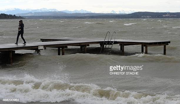 A woman carries a dog as she walks over a bridge at the lake Ammersee in the small Bavarian village of Herrsching southern Germany as stormy weather...