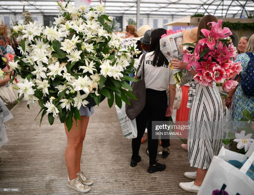 A woman carries a flowers during the 'Great Plant Sale' on the final day of the 2018 Chelsea Flower Show in London on May 26, 2018. - The Chelsea flower show, held annually in the grounds of the Royal Hospital Chelsea, opens to the public on May 22.