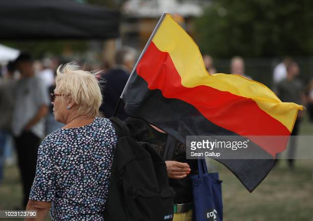 A woman carries a German flag with its colors in reverse order which she said was on purpose and in reference to the 1832 Hambach Festival which...