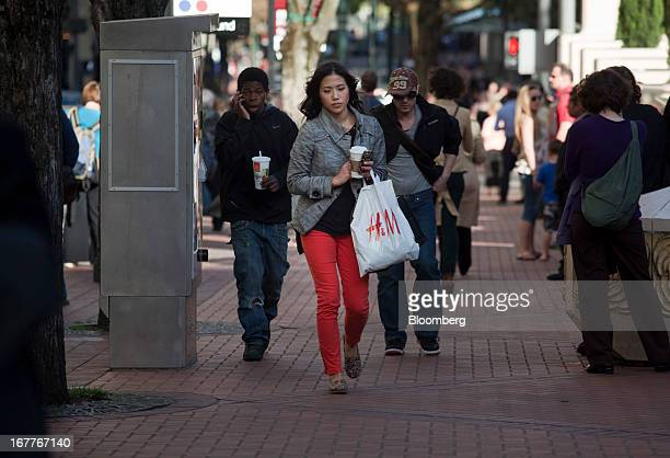 A woman carries a Hennes Mauritz AB shopping bag while walking down the street in Portland Oregon US on Wednesday April 24 2013 The US Conference...