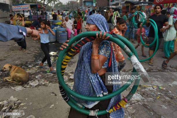 Woman carries a length of hose pipe to be used to fill water from a Delhi Jal Board tanker, at Sanjay Colony in Okhla Phase II, on June 11, 2019 in...