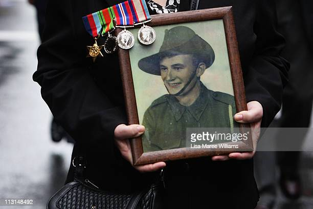 A woman carries a photo of a relative during the ANZAC Day parade on April 25 2011 in Sydney Australia Veterans dignitaries and members of the public...