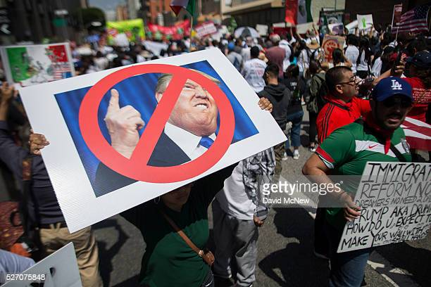 A woman carries a placard critical of Republican presidential candidate Donald Trump during one of several May Day marches on May 1 2016 in Los...