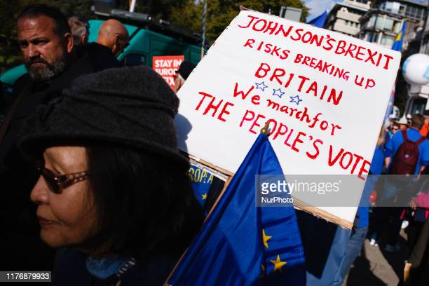 A woman carries a placard warning of the possible breakup of the United Kingdom after Brexit as demonstrators gather on Park Lane for the mass...