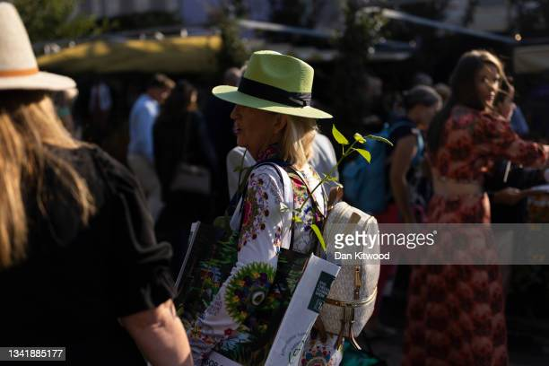 Woman carries a plant at Chelsea Flower Show on September 22, 2021 in London, England. This year's RHS Chelsea Flower Show was delayed from its usual...