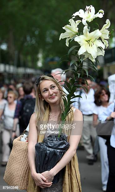 A woman carries a plant purchased on the last day of the Chelsea Flower Show on May 23 2009 in London The Royal Horticultural Society flagship flower...