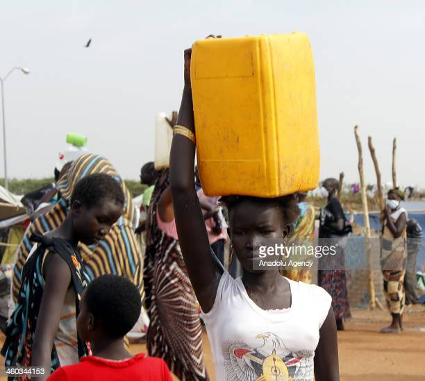 A woman carries a plastic can at the camp controlled by the United Nations on January 3 2014 in the town of Awerial South Sudan Thousands of people...