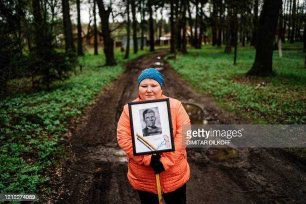 Woman carries a portrait of her grandfather near a monument dedicated to those who fought in World War II as Russians commemorate the 1945 victory...
