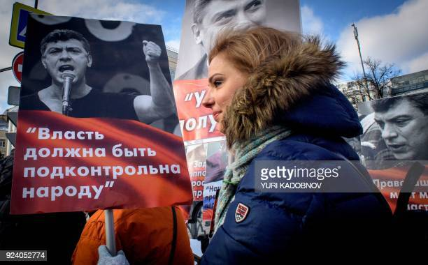 A woman carries a poster during an opposition march in memory of murdered Kremlin critic Boris Nemtsov in central Moscow on February 25 2018 The...