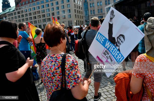A woman carries a poster reading Never Again and depicting AfD politician Bjoern Hoecke making a Nazi salute as he attends a demonstration titled...