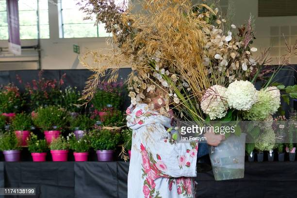 A woman carries a pot of flowers and grasses as she sets up her display during staging day for the Harrogate Autumn Flower Show on September 12 2019...