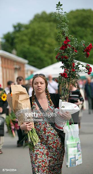 A woman carries a pot of flowers purchased on the last day of the Chelsea Flower Show on May 23 2009 in London The Royal Horticultural Society...