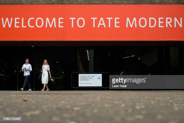Woman carries a protective face mask in her hand as she leaves the Tate Modern gallery on July 27, 2020 in London, England. The gallery on London's...