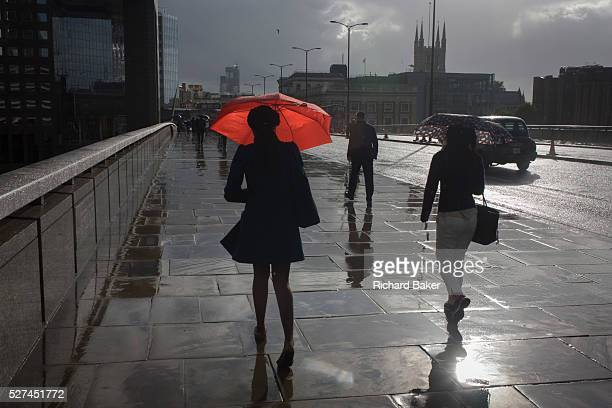 A woman carries a red umbrella crosses London Bridge in the rain southwards from the City on the north bank of the river Thames to Southwark on the...