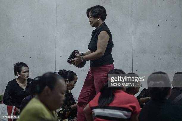 A woman carries a rooster for offerings during the Monolibabow rituals in Damat in the district of Tamparuli in Malaysia's Sabah state on Borneo...