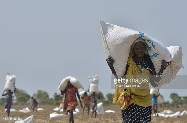 A woman carries a sack of food aid after a fooddrop in a field on February 23 2015 at a village in Nyal Panyijar county near the northern border with...