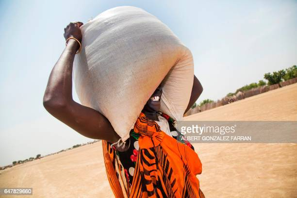 TOPSHOT A woman carries a sack of food distributed on March 4 in Ganyiel Panyijiar county in South Sudan South Sudan was declared the site of the...