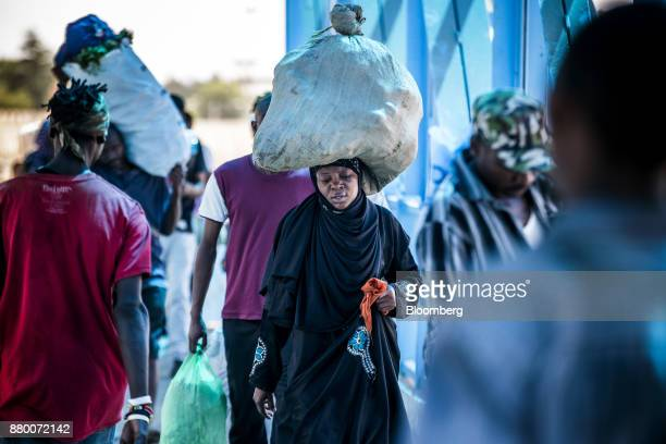 A woman carries a sack of goods on her head as she departs a market in Mombasa Kenya on Thursday Nov 23 2017 The countrys Treasury has already cut...