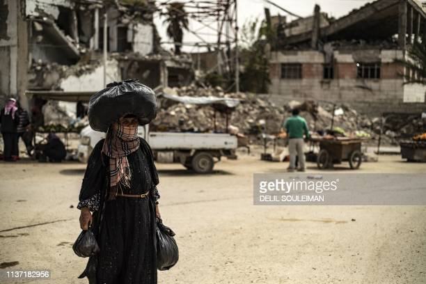 TOPSHOT A woman carries a sack on her head as she walks in front of damaged buildings in the northern Syrian city of Raqa the former Syrian capital...