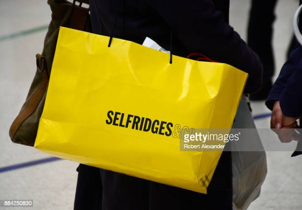 Woman carries a Selfridges & Co. Shopping bag as she walks down a London, England, sidewalk. Selfridges, also known as Selfridge & Co., is a chain of...